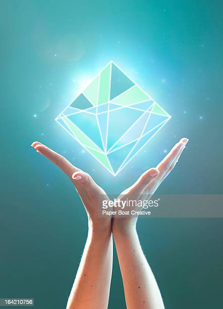 Hands supporting a glowing abstract blue cube
