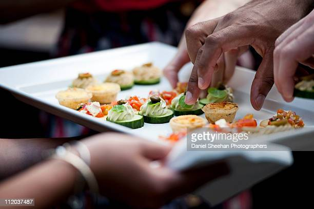 Hands taking canapes from plate
