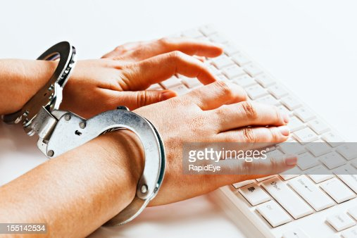 Hands tied unable to write freely on computer in handcuffs