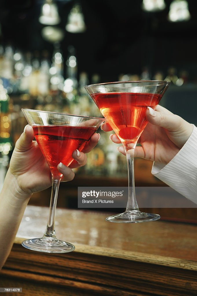 Hands toasting cosmopolitans : Stock Photo