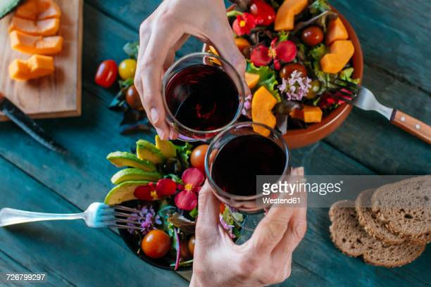 Hands toasting with glasses of red wine, close-up
