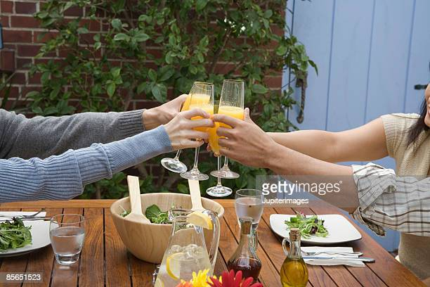 Hands toasting with mimosas