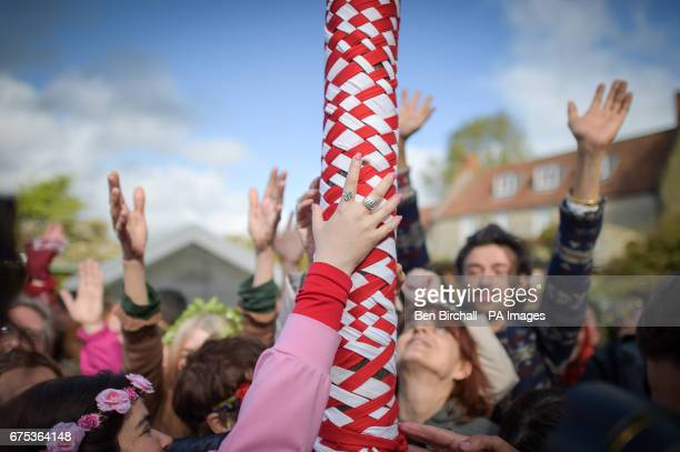 Hands touch the maypole at the Chalice Well Glastonbury where Beltane festivities are taking place on May Day