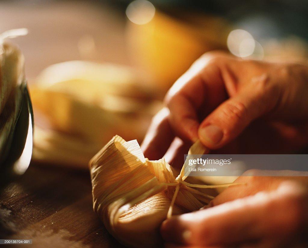 Hands tying corn husk tie around tamale, close-up : Stock Photo