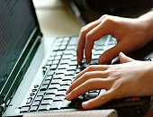 Hands typing on laptop keyboard.