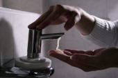 GERMANY BONN Hands under soap dispenser with liquid soap before washing the hands