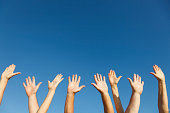 Group of people with their arms raised.
