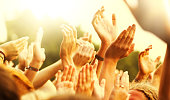 Large party group of people holding their arms and hands high in the air during an Outdoor Concert