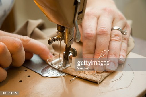 Hands using a sewing machine to sew brown material