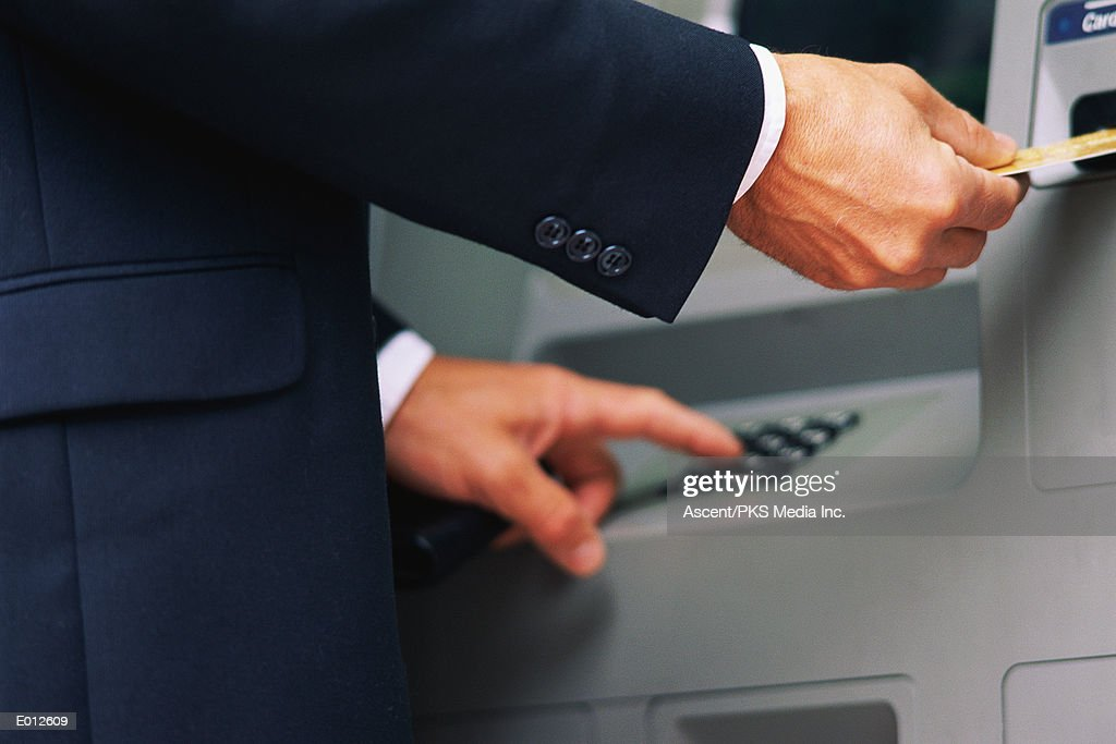 Hands using ATM machine