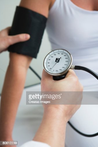 Hands using blood pressure cuff : Stock Photo