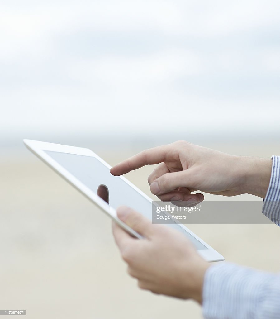 Hands using digital tablet at beach. : Stock Photo