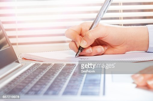 Hands using laptop and making notes on notepad : Stock Photo