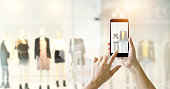 Hands using mobile smart phone and take a photo in display view of a clothing store, shopping online concept