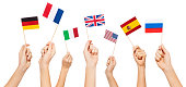 Hands waving small paper flags of USA and European Union member-states, isolated on white
