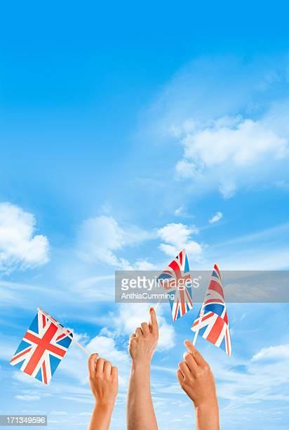 Hands waving union jack flags against a blue sky