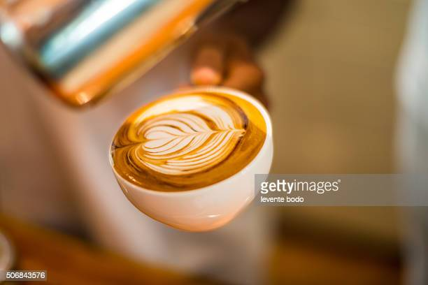 Hands with coffee on a wood table