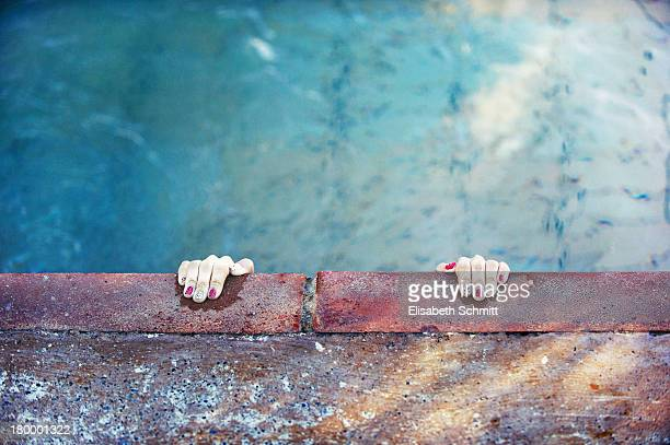 Hands with fancy nail polish at swimming pool