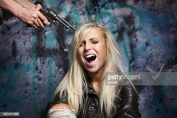 Hands with Gun Aiming at Young Terrified Girl