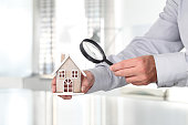 Hands with house and magnifying glass, search home concept