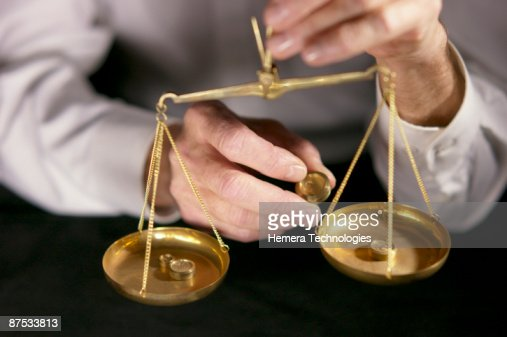 Hands with money and scales : Stock Photo