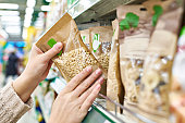 Buyer hands with the packaging of pine nuts in the store