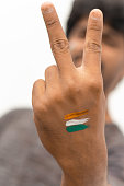 Hands with painted Indian flag showing Victory or V signed gesture.