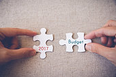 Hands with puzzle pieces and '2017 Budget' words,
