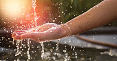 Hands with water splash, backlit by the evening sun.