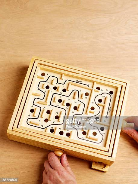 Hands with wooden Labyrinth puzzle