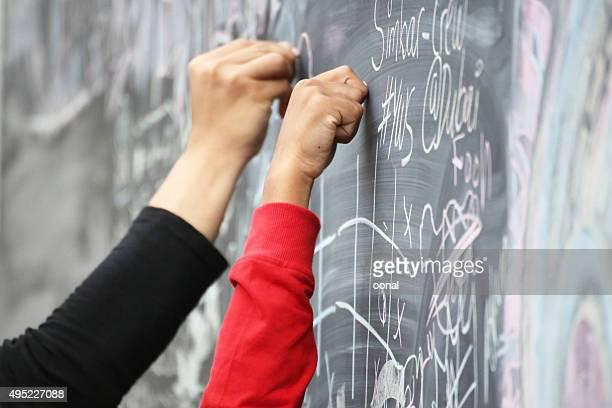 Mains écriture sur tableau noir avec CRAIE