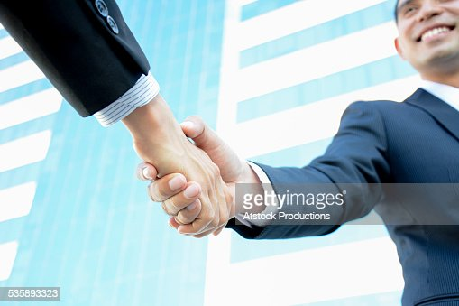 Handshake of businessmen with smiling face : Stock Photo