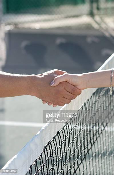 Handshake over tennis net