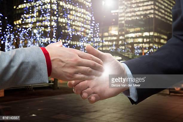 Handshake with energy glow between hands.
