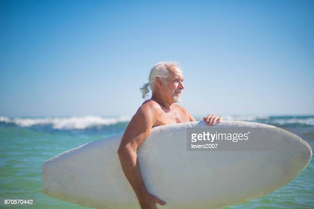 Handsome active senior surfing