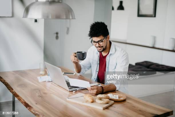Hübscher erwachsenen Mann durchläuft Finanzen vom frühen Morgen