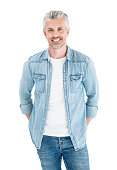 Portrait of a handsome adult man with grey hair dressed in denim and looking at the camera smiling - isolated over white
