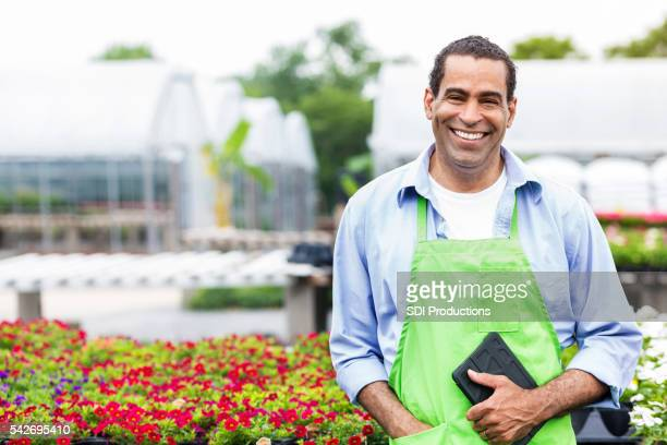 Handsome African American plant nursery owner holding tablet