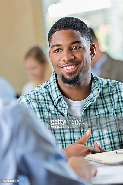 Handsome African American young adult smiling during job interview
