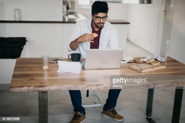 Gut aussehend Afrikaner Mann ist Laptop verwenden, um Nachrichten zu lesen, während des Essens einer Croissants