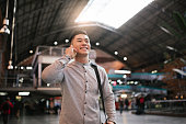 Handsome asian man using mobile in the train station. Communication concept.