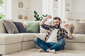 Handsome attractive bearded young men wearing casual shirt and jeans, sitting at home on carpet, listening to music in headphones, raising hands up