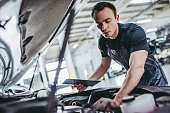 Handsome mechanic in uniform is examining the car while working in auto service. Car repair and maintenance.
