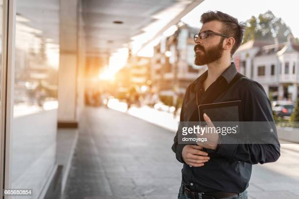 Handsome bearded businessman in the city street holding digital tablet