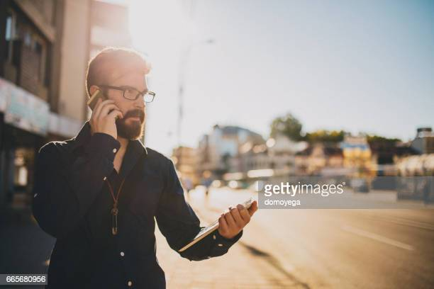 Handsome bearded businessman using digital tablet outdoors