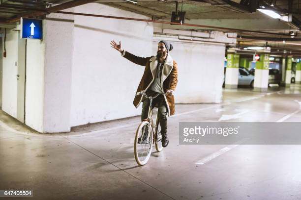 Handsome bearded hipster riding vintage bike in the parking lot