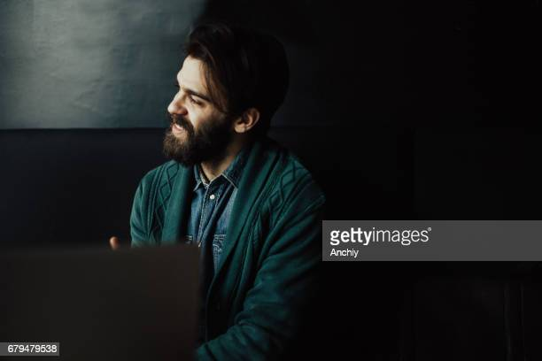 Handsome bearded man in the bar looking through the window