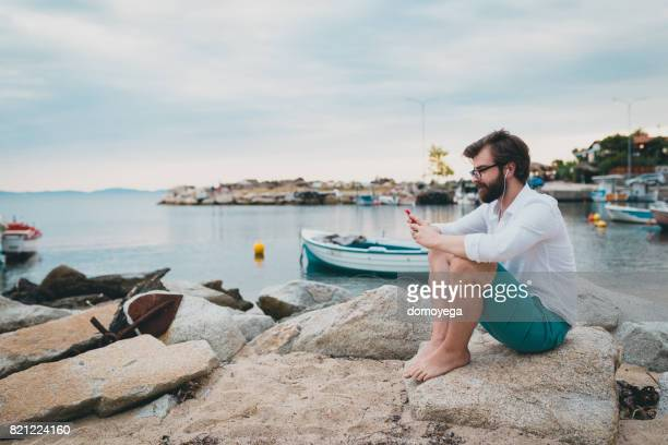 Handsome bearded man using phone and listening music by the sea