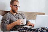 Relaxing morning. Young man wearing glasses drinking his coffee while working with a laptop in bed.