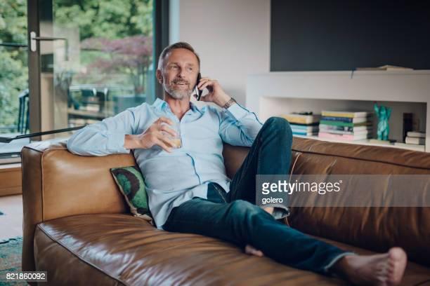 handsome bearded midaged man talking on mobile at sofa